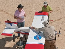 Several NASA Dryden Remotely Operated Integrated Drone (DROID) project team members secure the aircraft's single-piece wing during flight tests of the project's miniature ground collision avoidance system for small unmanned air vehicles.